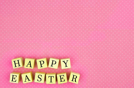 decorative design: Pink polka dot background with Happy Easter wooden blocks Stock Photo