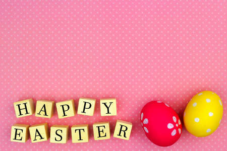 festive background: Happy Easter wooden blocks with Easter eggs against a pink polka dot background