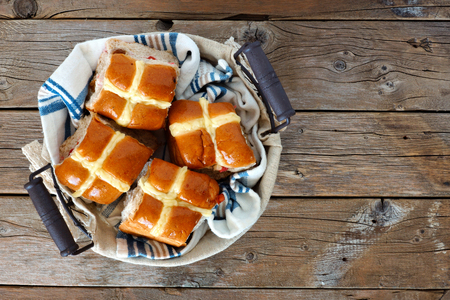 downward: Easter Hot Cross Buns in a basket, downward view on a rustic wood background