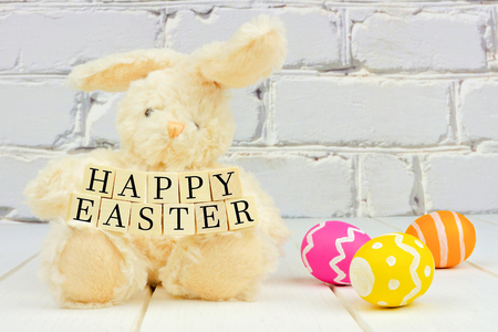 easter message: Toy Easter bunny holding Happy Easter wooden blocks with eggs against a white brick background Stock Photo