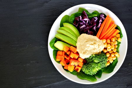 black dish: Healthy nourishment bowl with super-foods and fresh mixed vegetables, overhead view on dark slate Stock Photo
