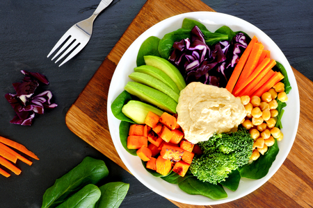 downward: Healthy lunch bowl with super-foods and fresh mixed vegetables, overhead scene on slate