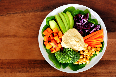 Nutritious lunch bowl with avocado, hummus and mixed vegetables, overhead view on wood