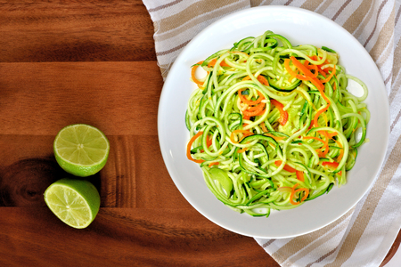 low calories: Healthy low carb zucchini noodle dish with carrots and lime on wood background, overhead view
