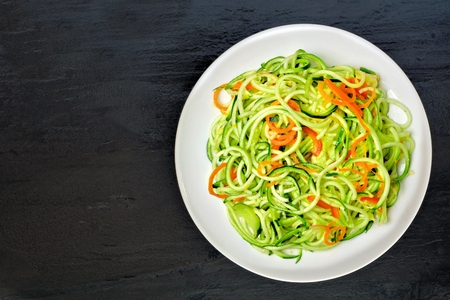 low calories: Low carb zucchini noodle dish with carrots and lime on dark slate background, overhead view