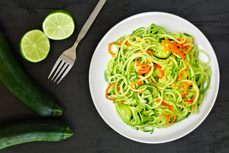 Healthy zucchini noodle dish with carrots and lime on dark slate background, overhead view