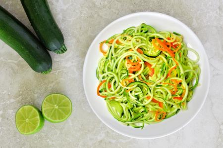 canicas: plato de fideos de calabacín con zanahorias sana y cal en el fondo de mármol blanco, vista aérea