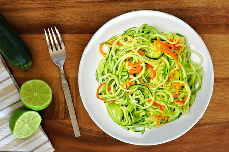 low: Healthy zucchini noodle dish with carrots and lime on wood background, overhead view Stock Photo