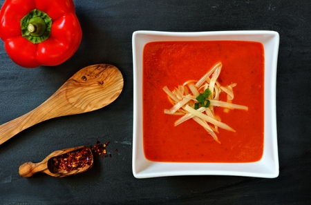 shredded cheese: Red pepper soup topped with shredded cheese and green onions overhead scene on a slate background