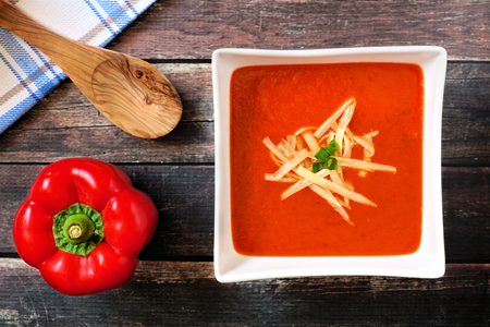 shredded cheese: Red pepper soup with shredded cheese and green onions in a square bowl overhead scene on rustic wood Stock Photo