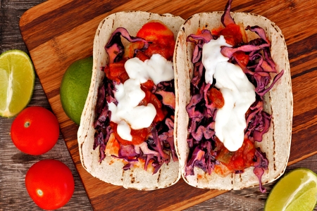 Sour cream: Two spicy fish tacos with red cabbage lime slaw, salsa and sour cream, downward view on wooden board