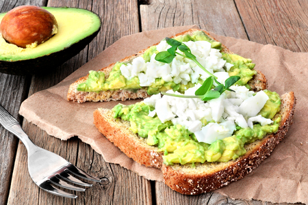 Avocado toast with egg whites and pea shoots on paper against a rustic wood background