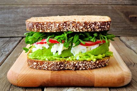 whites: Superfood sandwich with avocado, egg whites, radish and pea shoots on whole grain bread against a rustic wood background Stock Photo