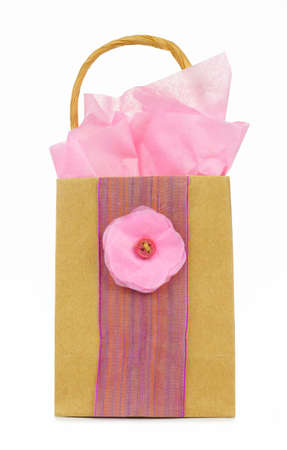 handcrafted: Hand decorated rustic gift bag with pink bow, tissue wrap and flower isolated on white