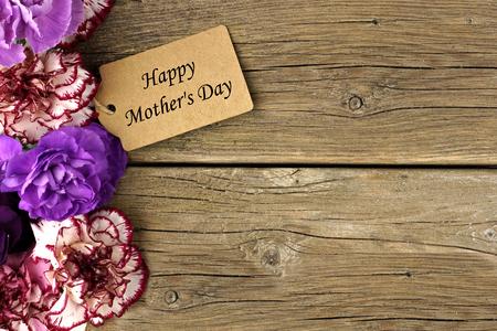 Feliz etiqueta del regalo del día de madres con la frontera del lado de la flor del clavel en el fondo de madera rústica