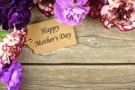 madre: Feliz etiqueta del regalo del día de madres con la frontera de la esquina de la flor del clavel en el fondo de madera rústica Foto de archivo