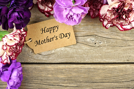 Happy Mothers Day gift tag with carnation flower corner border on rustic wood background Stockfoto
