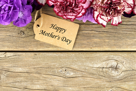 Happy Mothers Day gift tag with carnation flower top border on rustic wood background Stock Photo