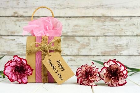 Moedersdag cadeau zakje met tag en mooie anjer bloemen tegen een rustieke witte houten achtergrond