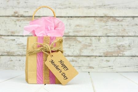 Handgemaakte Mothers Day gift bag met tag tegen een rustieke witte houten achtergrond Stockfoto