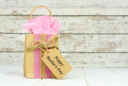 Handmade Mothers Day gift bag with tag against a rustic white wood background