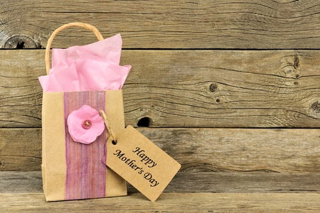 Handmade Mothers Day gift bag with tag against a rustic wood background Stock Photo