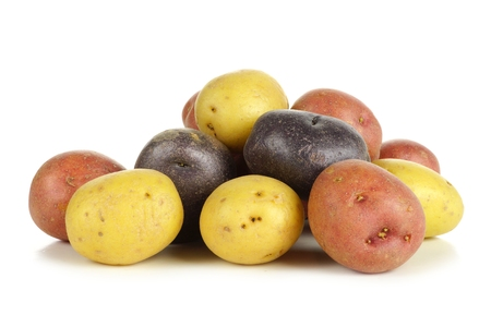 Pila de coloridos pequeñas patatas frescas sobre un fondo blanco