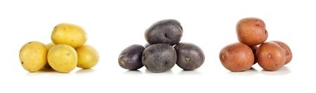 papas: Tres montones de pequeñas patatas frescas de color amarillo, púrpura y rojo sobre un fondo blanco