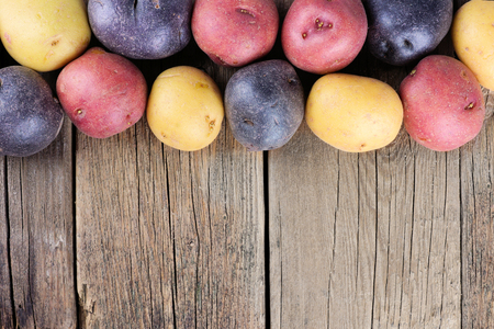 potatoes: Top border of colorful fresh little potatoes over a rustic old wooden background