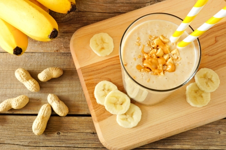 Peanut butter banana oat smoothie with paper straws, on a wood board on rustic table, downward view Archivio Fotografico