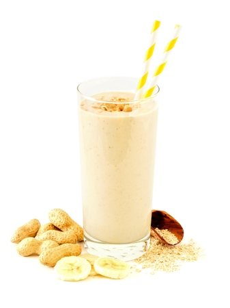 Peanut butter banana oat smoothie in a glass with straws and scattered ingredients over a white background Stockfoto