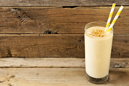 fruit shake: Peanut butter banana oat breakfast smoothie with paper straws against a rustic wood background Stock Photo