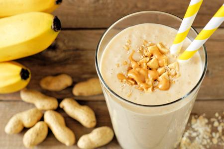 cacahuate: La mantequilla de maní licuado de avena de plátano con la paja de papel en la mesa rústica con los ingredientes dispersos