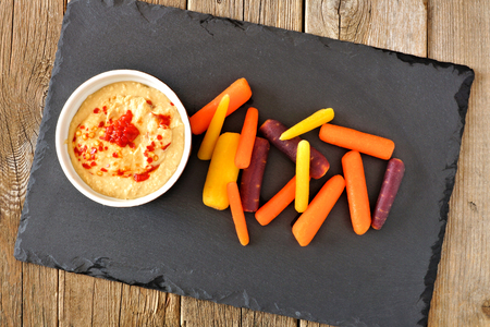 Baby rainbow carrots with hummus dip on a slate server over a rustic wooden background