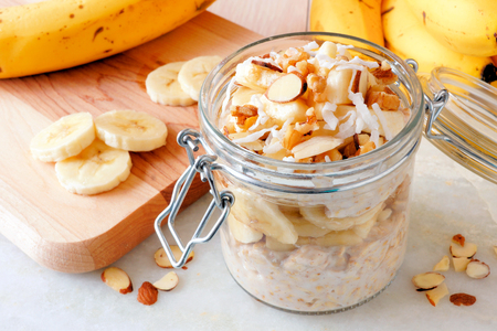 oats: Overnight oats with bananas and nuts in snap lid glass jar on white marble Stock Photo