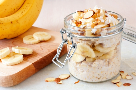 Banana nut overnight oats in snap lid glass jar on white marble