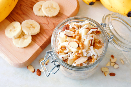 oats: Banana nut overnight oats in glass canning jar on white marble, downward view