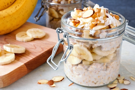 overnight: Healthy overnight oats with bananas and nuts in glass canning jars
