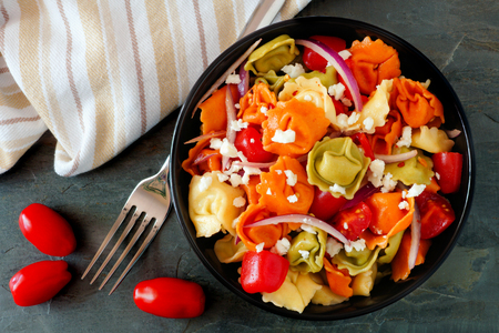 Colorful tortellini pasta salad with tomatoes and onions, overhead scene on dark slate