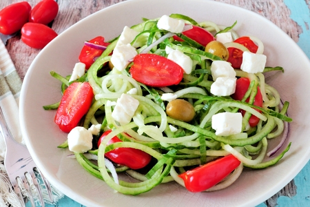 Fresh Greek Salad with cucumber noodles close up on vintage plate Stock Photo