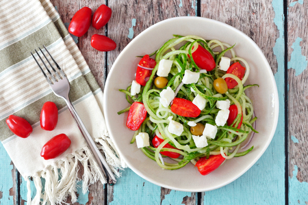 carb: Fresh Greek Salad with cucumber noodles, overhead scene on rustic wood background Stock Photo