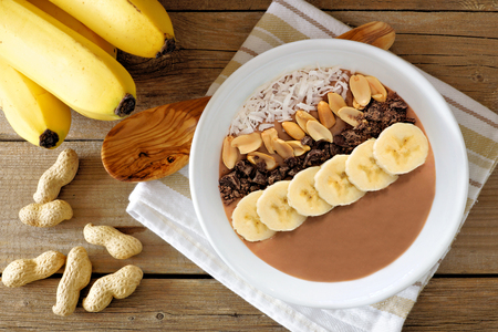 bowls: Chocolate peanut-butter banana, smoothie bowl overhead scene on rustic wood background