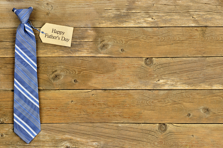 single father: Happy Fathers Day gift tag with blue striped necktie on rustic wood background
