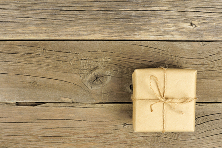 handcrafted: Brown paper wrapped gift box with twine bow on a rustic wood background