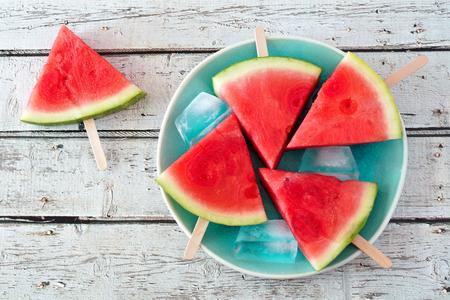 Watermeloen plakjes popsicles op een vintage blauwe plaat en rustieke houten achtergrond