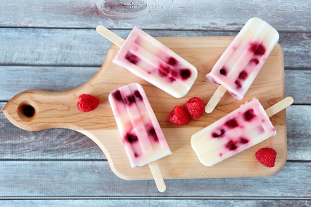 Homemade raspberry vanilla popsicles on a paddle board with rustic wood background