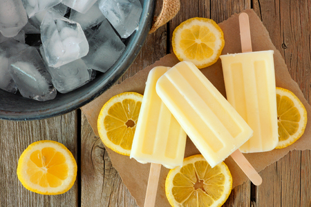 Homemade lemon yogurt popsicles with fresh lemon slices on paper with rustic wood background Stock Photo