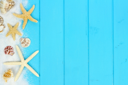 Summer side border of sand, sea shells and star fish on blue wooden background