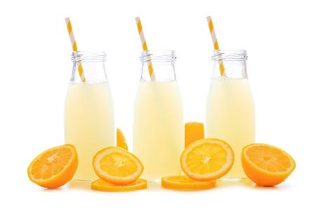 vaso con agua: Tres botellas de limonada fría con rodajas de limón y la paja aisladas sobre un fondo blanco Foto de archivo