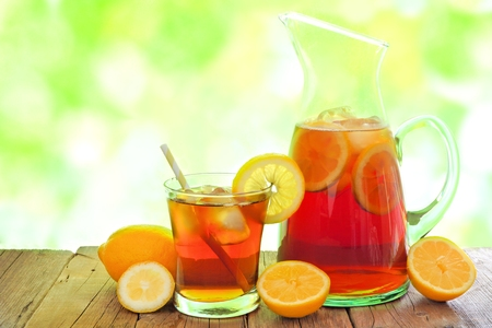 tea table: Pitcher of iced tea with glass and lemon slices against a defocused outdoors background